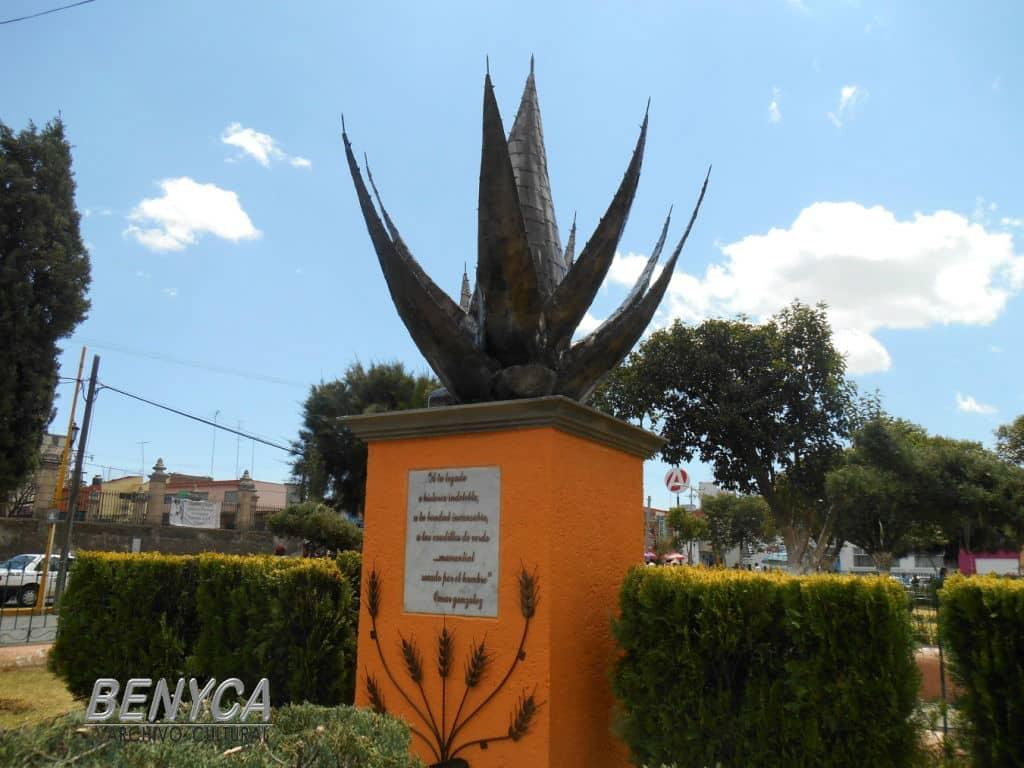 Escultura al Maguey en el jardín principal de la ciudad de Apan , Hidalgo, con un fondo azul celeste.